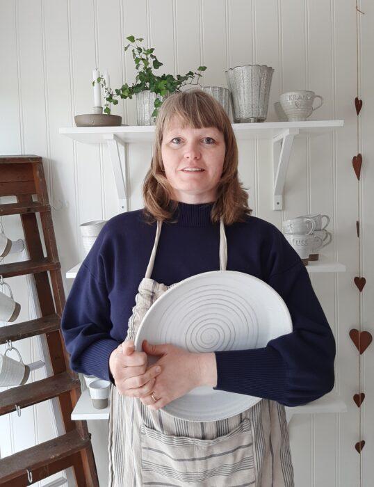 Hele Andersson keramiker på Helena af Hyltarp keramik. I famnen håller jag ett stort handdrejat fat med tydliga drejränder.