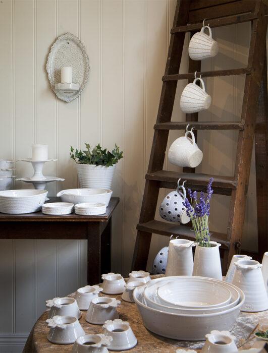 Gårdsbutik med en hörna med vitglaserad keramik. Här hänger de handgjorda kopparna på krokar på en stege och gårdens lavendeln står i blomvaserna.