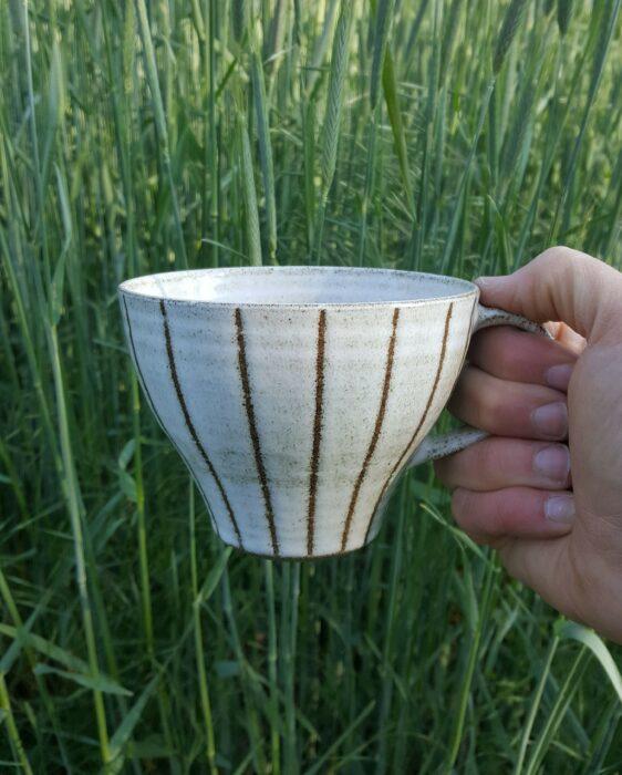 Handgjord keramik. Den randiga koppen Agda är drejad i grå lera och doppad i vit glasyr. Ränderna är skapade med hjälp av billackeringstejp. Bakgrunden är vårt vackra gröna rågfält.